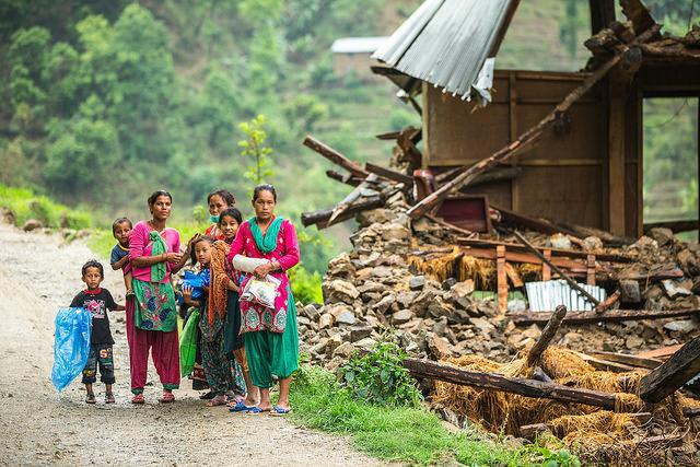 A family beside a damaged house near Naglebhare, Nepal.